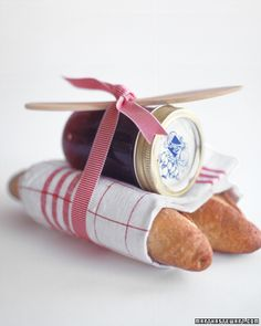 Jam Gift Package: This small, thoughtful gift is a good way to thank a hostess. Wrap two loaves of your favorite crusty bread (like French baguettes) in a linen dish towel, and top with a jar of homemade jam. Tie them together with a colorful ribbon to match the towel, securing a wooden spreader in the knot of the bow.