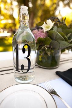 DIY Table Numbers For Every Wedding Style: Adding number decals to glass bottles easily helps guests find their table and stay refreshed, too!   Source: Ashley Davis Photography via Style Me Pretty