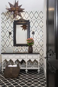 A black door opens to a Moroccan style bathroom clad in black and white marble quatrefoil floor tiles leading to a woven basket placed in front of a whitewashed washstand contrasted with a black quartz countertop finished with an overmount metal sink.
