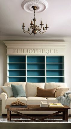 Use peacock blue to brighten an austere living room (or a softer, cozier one; it's versatile like that) | bookcase ideas | wood coffee table | chandelier