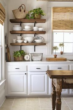 three heavy, open restaurant-style shelves holding a variety of plates and bowls, with straw baskets and a green plant on top, hung in a bright kitchen with white cabinets for the must-have, money-saving kitchen upgrades gallery