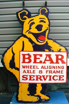 Die-Cut sign advertising Bear Wheeling Alignment & Service. Yellow bear holding a sign. This signs mounting point are two hangers that come out above the ears.