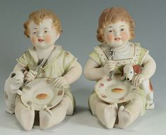 Pair of large painted biscuit porcelain piano baby figures, modeled as twin boy and girl, each holding a lustre-painted spoon and floral-painted dish, accompanied by a dog and cat. Crazy Cat Lady, Crazy Cats, Piano, My Doll House, Boy Dog, Twin Boys, Vintage Decor, Vintage Stuff, Old Dolls