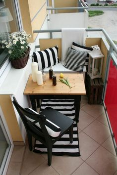 Tiny terrace corner with black and white prints, flowers and candles for a cozy and romantic look