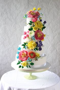 4 tier white wedding cake with bright colored flowers