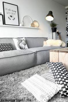 Pokój dzienny urządzony  z minimalizmem w skandynawskim stylu. Półeczki ribba z Ikei są fajnym pomysłem na postawienie obrazków, zdjęć czy innych drobnych dekoracji. Wystarczy powiesić ją nad łóżkiem czy sofą i wyeksponować choćby książki. Do tego drewniany stolik.