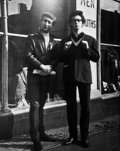 John Lennon and Paul McCartney pose on the streets of Liverpool before fame and mop top hairstyles take hold.
