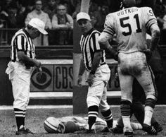 Dick Butkus stands over Chuck Hughes after he collapses on field during a game - he died of a heart attack - only player to die in an NFL game - this is a very rare photo as the league suppressed images of this event