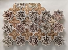 Panel Composed with Tiles in Shape of Eight-pointed Stars and Crosses Object Name: Star-shaped tile Date: 1260–70 Geography: Iran, probably Kashan Medium: Stonepaste; luster-painted on opaque white glaze under transparent glaze Dimensions: 8 in. (20.3 cm) Wt. (whole group) 51 lbs. (23.1 kg) Classification: Ceramics Credit Line: H.O. Havemeyer Collection, Gift of Horace Havemeyer, 1941 Accession Number: 41.165.22