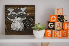 String art woodland raccoon creature purchased from Etsy, white geometric succulent pot, and House Industries Neutraface blocks from our woodland adventure themed nursery in grey, white, orange, and mint.