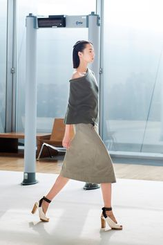 28. Short cape in knitted extrafine wool, flared skirt in broken twill, heeled open sandals in leather