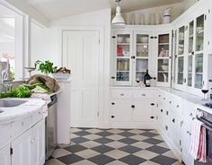 a black and white tile floor in a white kitchen