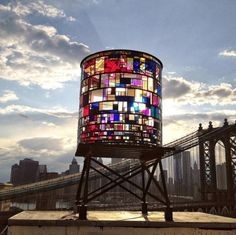 The sculpture by DUMBO-based artist Tom Fruin hovers next to the Manhattan Bridge from atop a 11-story building he works out of at 20 Jay Street.