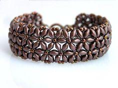 Náramok vyrobený z matných voskovaných hnedýchn korálok. Šmrnc mu dodávajú lesklé hnedé maličké korálky.  Zapínanie z bižutérneho kovu....