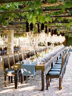 Incredible long tables set beneath a grape canopy, complete with chandeliers. So pretty.