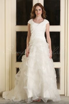 Wedding Dress by SimplyBridal. A voluminous organza skirt defines this bridal gown with its beautifully crafted ruffles and dramatic A-line silhouette. A simple scoop neck and glossy taffeta bodice prevent this gown from becoming too busy with minimal embellishments and modest cap slee. USD $377.99