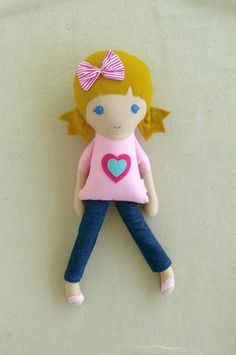 This is a handmade cloth doll measuring 20 inches. She is wearing a sweet, light pink t-shirt with a felt heart appliqué, dark denim jeans, and pink sandals. Her golden blond hair is worn in low, pointed ponytails and accented with a hot pink and white striped fabric bow. She is made from 100% cotton fabrics, wool blend felt, and polyester fiberfill. Her seams are triple stitched and she is firmly stuffed with Polyfil.   Please hand wash or machine wash on gentle cycle. Lay flat to dry…