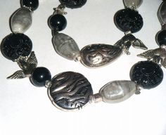 """A lovely big chunky necklace in shades of dark silver grey and black. Metal, glass & acrylic beads in rounds coins dimpled ovals and winged hearts. 36.1/2"""" long"""