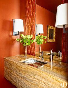 The powder room features a vanity made of Macaubas Gold quartzite.