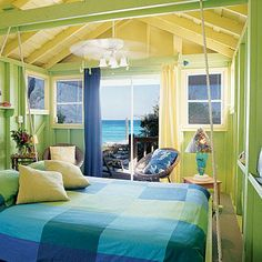 This bright, colorful bedroom boasts green walls, a yellow ceiling, and blue bedding. Coastalliving.com