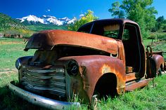 An abandoned truck with the San Juan Mountains in the background; the location is near Ridgway, Colorado.