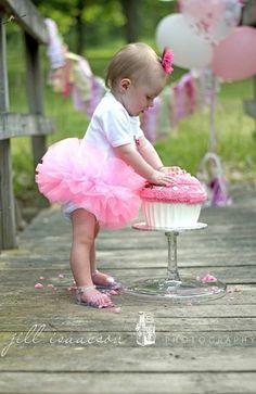 Baby in pink tutu crushing a cupcake