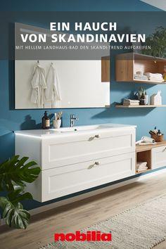 Ein Hauch von Skandinavien weht durch dieses Bad aus dem nobilia Programm Cascada: Die facettierten, matten Lackfronten sind das Aushängeschild für den modernen Landhausstil, erinnern im Zusammenspiel mit Holzdekoren aber auch an den Trendlook Skandi. Das Ergebnis: ein helles Badezimmer, das förmlich dazu einlädt, sich zu entspannen und das beleuchtete Ambiente zu genießen. #nobilia #badinspiration #landhausstil Bad Inspiration, Trends, Storage Chest, Cabinet, Furniture, Home Decor, Bright Bathrooms, Modern Country, Home
