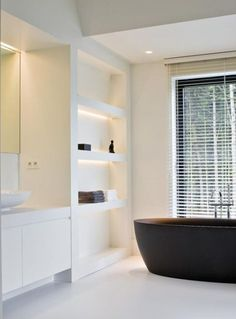 LED under shelf lighting, white contemporary bathroom, black free standing bath