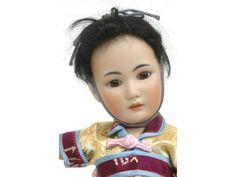 Poupée de type asiatique par Simon & Halbig, tête porcelaine moule 1329, taille 4, bouche ouverte avec dents dans le haut, yeux fixes marron, corps articulé d'origine, habits de style et perruque. H. 33 cm.
