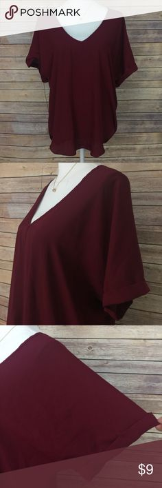 """Living Doll Short Sleeve Sheer Burgundy Blouse Worn once, like new. High in the front, low in the back. Bust is 40"""". Length is about 26"""". 100% Polyester 🚨 Look closely at the photos to know what exactly you are receiving and the condition that it's in! Smoke/Pet free home. Prices $13 and under are firm. Bundle 2+ of my items to save 15%. I do not trade or hold items. Check out my websites on my profile. Living Doll Tops Blouses"""