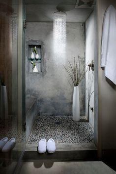 Concrete and pebble stone shower in a loft bathroom   (via Delancey Street Loft)