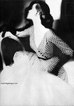 1950's trends: the polka dots, V-neck styling, asymetrical buttoned bodice, self-belted waist & flaring, floaty skirt.