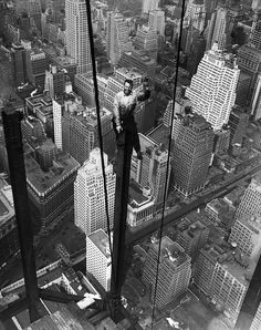 Steelworker Carl Russell waves for the camera while working on the 88th floor of the Empire State Building. NYC, 1931