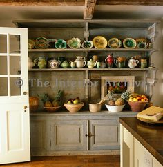 A 19th century French dresser found in a bakery in the Dordogne displays a collection of earthenware and majolica against one wall of this r...