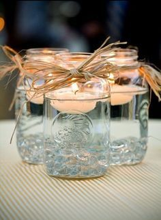 Mason jar centerpieces with floating candles. [UPDATED These DIY Mason Jar Centerpieces can also be made into favors. Use the lanterns to provide light to your wedding tables. Floating Candle Centerpieces, Rustic Wedding Centerpieces, Diy Centerpieces, Quinceanera Centerpieces, Easy Table Decorations, Wedding Favors, Wedding Tables, Simple Wedding Table Decorations, Wedding Ceremony