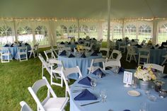 Inside of the tent at Earhart Manor - white wooden folding chairs and blue linens