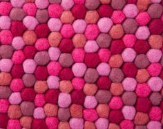 About felt ball rugs  The purplish-red of Aayusha is definitely eye-catching. It's extremely unique. The contrast between the reds, purples and pinks in this felt ball rug will not go unnoticed by you or your guests. Sometimes what a room needs is a big, complex and bold rug. We think the Aayusha delivers!