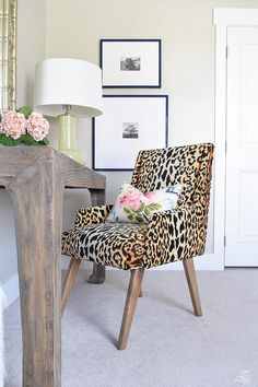 Chic work space boasts a leopard print chair in Tonic Home Bianca Fabric lined with an Eastern Charms Hibiscus Pillow paired with a salvaged wood desk topped with a yellow green lamp.