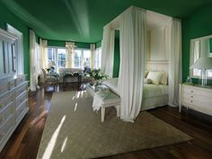 Love the drapes around the bed, and the green colored walls ..so great