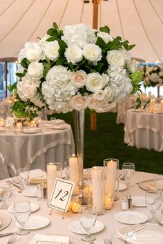 Tall table centerpiece for Cape Cod wedding.  Roses, hydrangeas, orchids with green accents.  Florist: Lilacs Florals Cape Cod Photo Credit: Nicole Friedler Photography