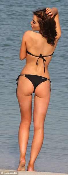 Just peachy: The model's itsy-bitsy bikini also offered a daring glimpse of her pert posterior as she turned around to flash her derriere in...