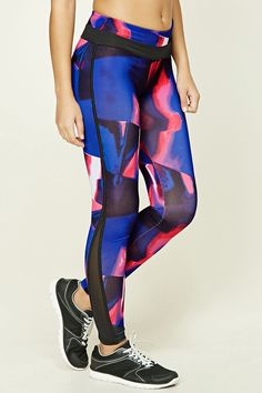 This pair of stretch knit athletic leggings features an abstract print, contrast piped trim, geo-shaped mesh inserts at the leg cuffs, moisture management, and a hidden key pocket on the elasticized waist.