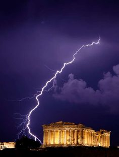 A flash of lightning illuminates the sky over the 2,500-year-old Ancient Parthenon temple, on the Ac... - AP