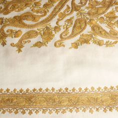 This traditional Kashmiri stole is handwoven in cream-coloured wool and has striking paisley motifs embroidered on it in rich gold and mustard shades. The embroidery is known as aari or crewel work. It is a speciality of Kashmiri artisans who create it in fine, concentric rings of chain stitch using a long hooked needle known as a crewel.