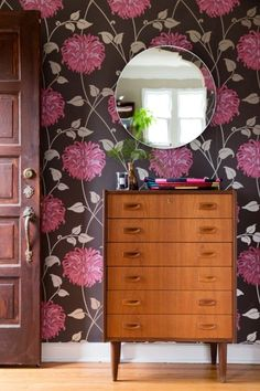 A vintage dresser stands out against a gorgeous floral wallpaper.
