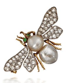 BAROQUE PEARL AND DIAMOND BEE BROOCH, MARCUS & CO., CIRCA 1900.  The body formed of two baroque pearls measuring approximately 10.5 by 10.8 mm. and 12.0 by 11.3 mm., the wings set old European-cut diamonds, completed by 2 round cabochon demantoid garnet eyes, mounted in platinum and gold, signed Marcus & Co.
