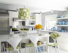 Jonathan Adler    eclectic white gray blue kitchen design with white, green and blue kitchen! White kitchen cabinets, white carrara marble counter tops, gray backsplash, green floral pendant kitchen island light, horse serving dish and white modern stools with green floral pattern.