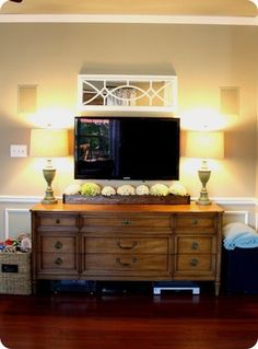 TV wall - substantial stand that gives weight to the space. Interesting mirror above TV makes it feel more decorative.