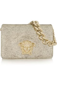 Stopping traffic is inevitable if you're carrying this glamorous clutch with glossy Medusa head crest and gold-flecked black suede.
