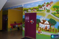 Grote muurschildering in de gang van een school